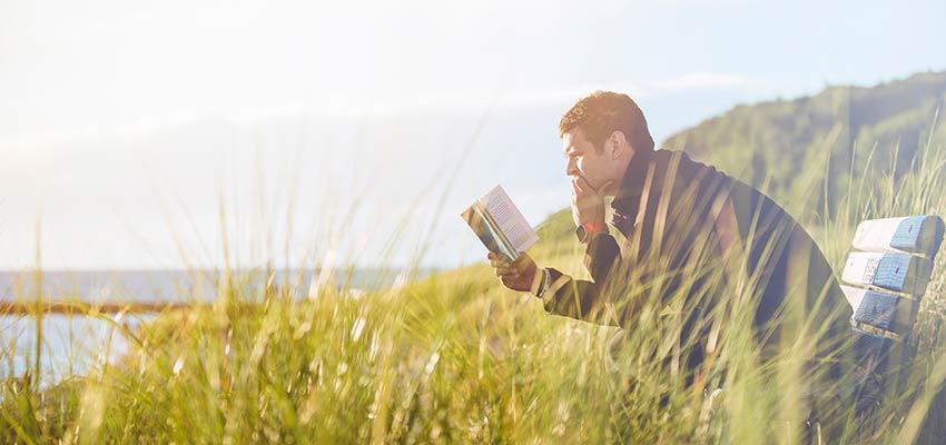 Un hombre leyendo afuera.