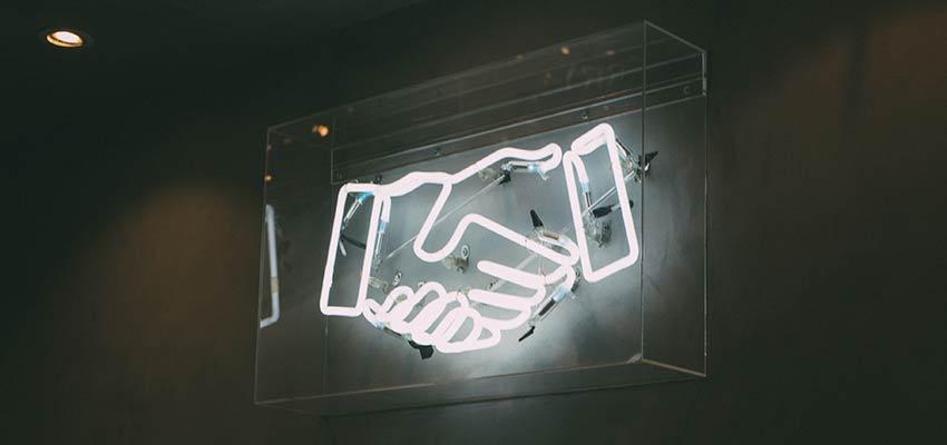 Bir əl sıxışmağı təmsil edən bir neon işarəsi.