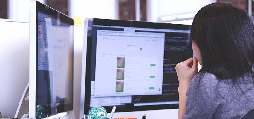 Menyw yn defnyddio cyfrifiadur monitor deuol.