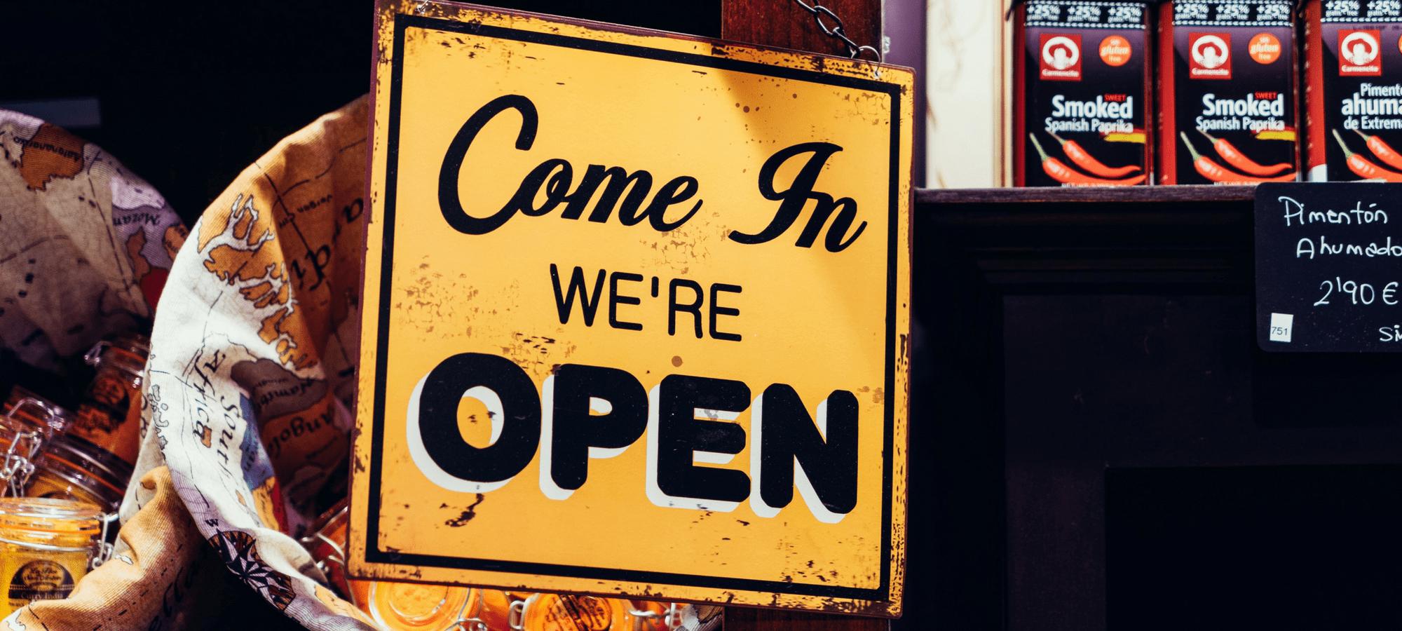 Estamos abiertos, letrero amarillo