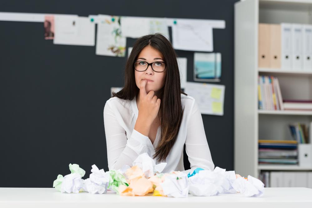 Mujer joven con bloque de escritores sentada en una oficina con un escritorio lleno de papel arrugado mientras se sienta mirando pensativamente en el aire con el dedo en la barbilla buscando nuevas ideas