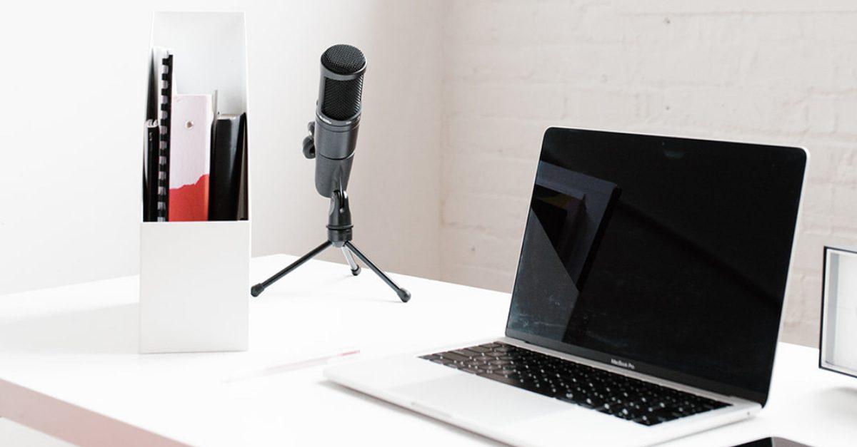escritorio blanco con laptop y micrófono