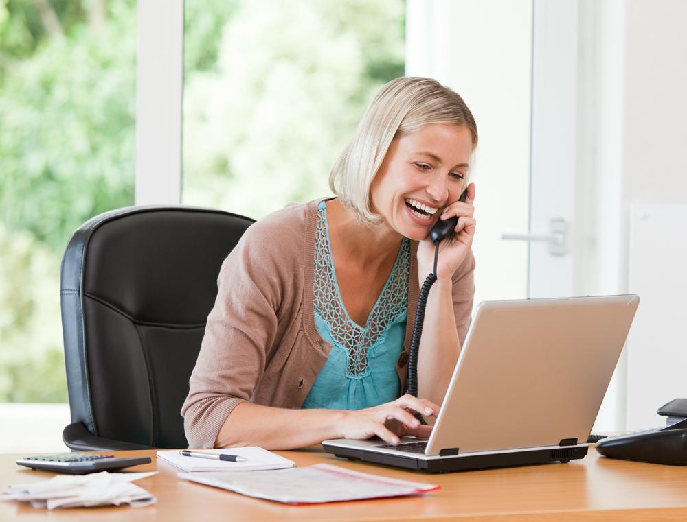 Mujer trabajando en su computadora mientras llama a su casa