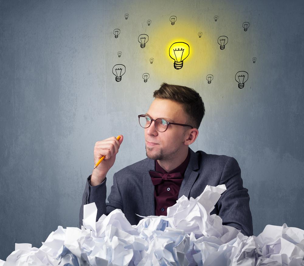 Joven empresario sentado detrás de papel arrugado con bombillas por encima de su cabeza