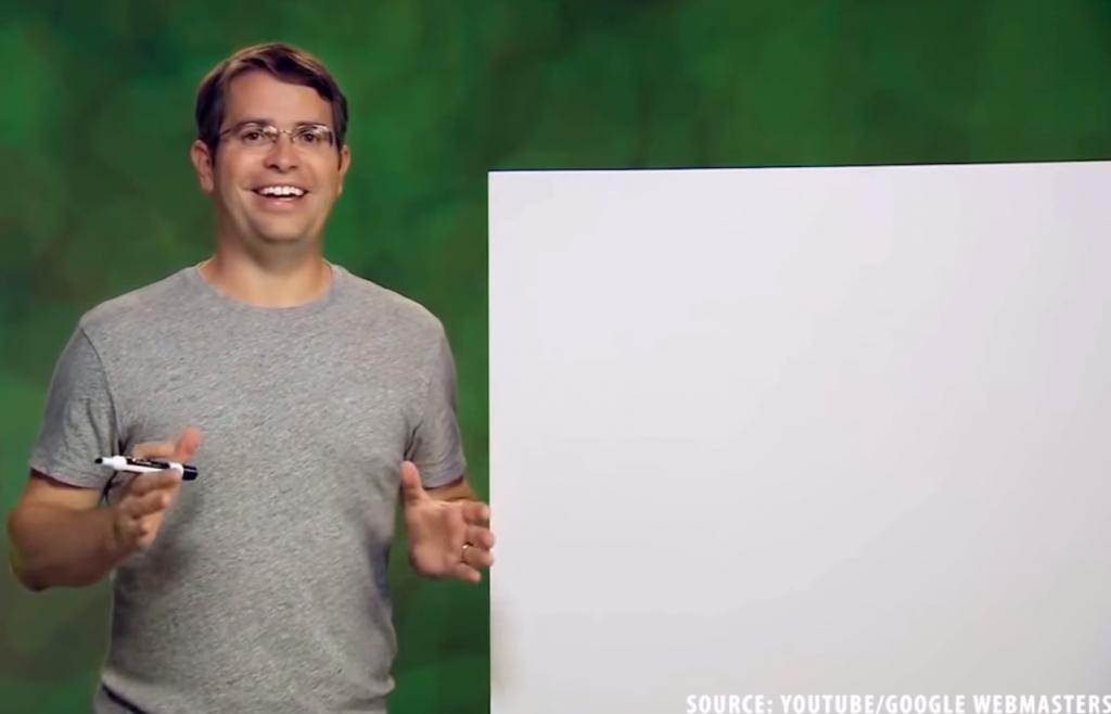 Fotograma de SEO: la película que muestra a Matt Cutts sosteniendo un marcador de pizarra junto a una pizarra en blanco, una explicación intermedia de un concepto. El crédito en la esquina inferior derecha dice 'Fuente: YouTube / Google Webmasters'.