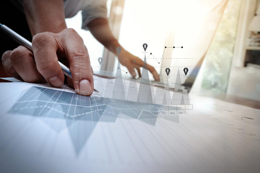 documentos de negocios en la mesa de oficina con teléfono inteligente y computadora portátil y negocios gráficos con diagrama de red social y hombre trabajando en segundo plano