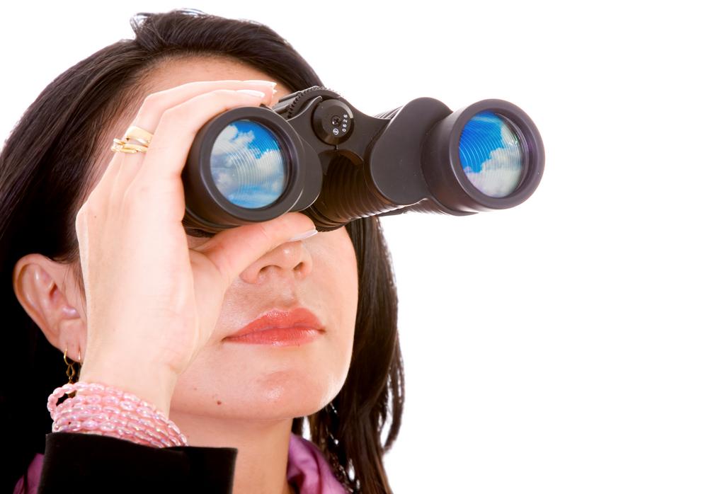 Mujer de negocios haciendo una búsqueda con sus binoculares - aislado sobre un fondo blanco.