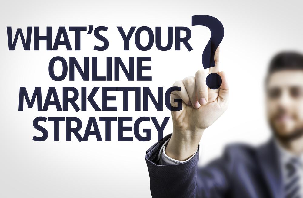 Hombre de negocios apuntando a tablero transparente con texto ¿Cuál es su estrategia de marketing en línea?