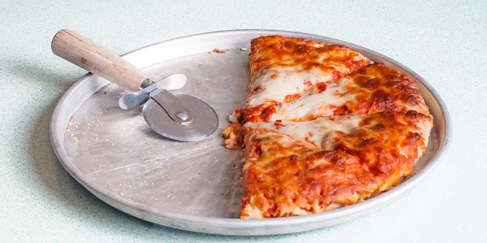 La mitad de una pizza de queso en una sartén con el cortador.