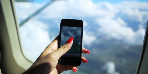 Teléfono inteligente tomando fotos en el avión