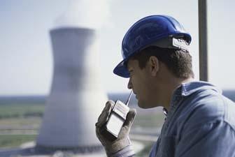 Perfil lateral de un trabajador hablando por un walkie-talkie en una central eléctrica