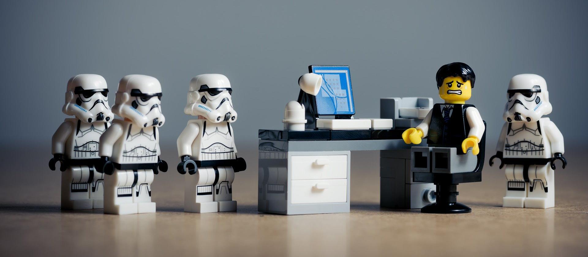 Soldados de asalto LEGO rodeando a alguien en un escritorio