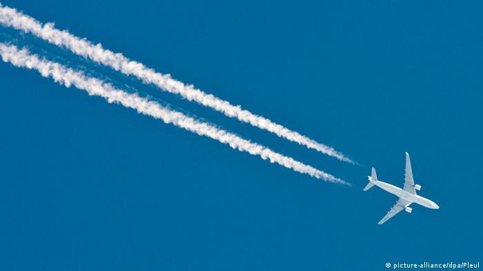 Un avión cruza un cielo azul profundo, dejando líneas blancas a su paso